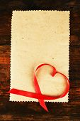 Blank sheet of paper with ribbon in heart shape on rustic wooden table background