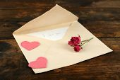 Envelope with love letter and dried rose on rustic wooden table background