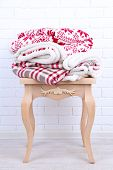 Warm plaids on small wooden table and white brick wall background