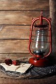 Kerosene lamp with dried rose and letter on wicker mat and wooden planks background