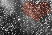 Rain water drops on window glass with heart