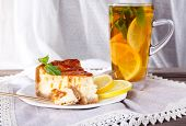 Cheese cake in plate and herbal tea on napkin on curtain background