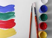Colorful paint strokes with brush and paint cans on white sheet of paper background
