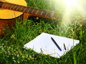 Photo guitar and notepad with pen on the grass
