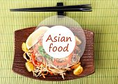 Chinese noodles with vegetables on plate and space for your text on bamboo mat background