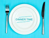 Plate with text Dinner Time, fork and knife on tablecloth background