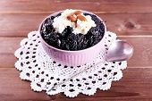 Dessert with prunes and almonds in bowl on lace doily and wooden planks background