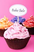 Delicious cupcakes with inscription on color background