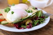 Sandwich with poached eggs, cheese and vegetables on plate on wooden background