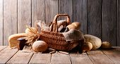 Different bread in wicker basket on table on wooden background