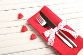 Fork and knife with decorative hearts on wooden table