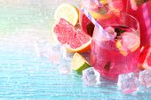 Pink lemonade in glasses and pitcher on bright background