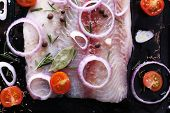 Pangasius fillet with spices and vegetables on firepan background