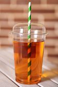 Apple juice in fast food closed cup with tube on wooden table and brick wall background