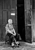 BANGKOK, THAILAND - DECEMBER 25, 2014: Street Photography of old woman with a cane in her hands sitting on a chair near the door of her house