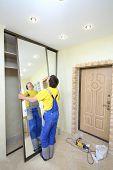 Worker puts mirror doors in closet in hallway