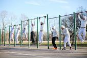 Eight young people hang on the horizontal bar on the playground