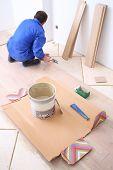 Man puts laminate flooring in white room
