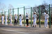 Eight young people near the long horizontal bar at the playground