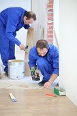 Two men in blue overalls laid parquet in the narrow room