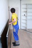 Man in workwear holding mirrored door on sliding wardrobe in room
