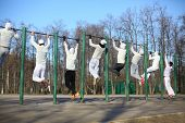 Eight young men training on the horizontal bar on the playground, view from the back