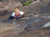 Rock climber climbing up a cliff.