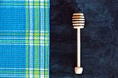honey stick and tablecloth over blackboard background