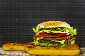 Delicious cheeseburger stacked high with a juicy beef patty, cheese, fresh lettuce, onion and tomato - space for text