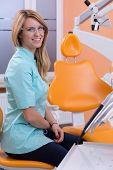 Dentist Sitting On Dental Stool