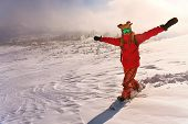 Snowboarder on the mountain with his arms raised