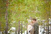 Attractive young couple in winterwear embracing in natural environment