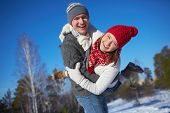 Cheerful girl and guy in knitted winterwear having fun in natural environment