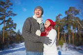 Ecstatic man and woman in knitted winterwear spending leisure in park