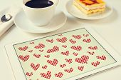 hearts drawn in a graphics editor of a tablet on a table set for breakfast
