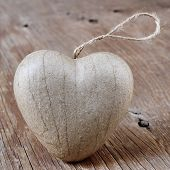 a brown cardboard heart on a rustic wooden surface