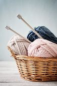 image of coil  - Wool yarn in coils with knitting needles in wicker basket on light blue background - JPG