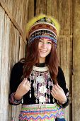 stock photo of hmong  - Traditionally dressed Mhong hill tribe woman in the wooden cottage - JPG