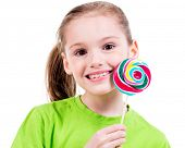 Portrait of smiling little girl in green t-shirt with colored candy - isolated on white.