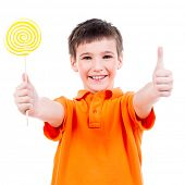 Happy boy in orange t-shirt with colored candy showing thumbs up sign - isolated on white.