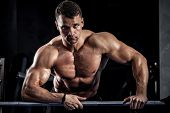 Brutal athletic man pumping up muscles with barbell