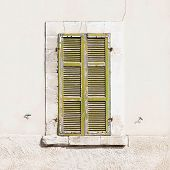 Old green closed window with shutters