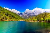 stock photo of jade blue  - A view of a river and Jade Dragon Snow Mountain in Lijiang  - JPG
