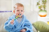 foto of teething baby  - Little baby boy with tooth brush in the living room - JPG