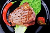 bbq : beef (pork) steak garnished with green lettuce and red chili hot pepper on black dish isolated over white background