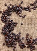 Heap Of Burnt Coffee Beans On Sackcloth Background