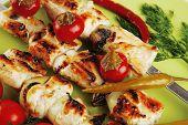 fresh roast shish kebab on green platter with vegetables
