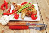 grilled meat : grilled quarter chicken garnished with red peppers on white plates over wooden table