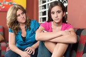 Worried and sad mother looks at her defiant teenage daughter