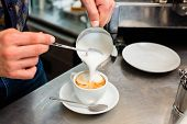Barista in cafe or coffee bar preparing proper cappuccino pouring milk froth in a cup